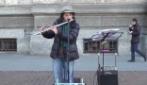Milano, artista di strada suona il flauto a Piazza della Scala
