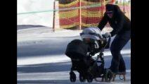 Discesa sulla neve in passeggino: neonata e papà sciatore giù per il pendio