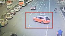 Una macchina rossa è ferma sulla carreggiata: dopo pochi secondi accade un incidente spaventoso