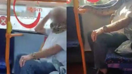 L'uomo sul bus non indossa la mascherina: copre la bocca con un serpente