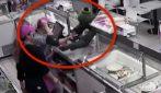 Il rapinatore abbassa la guardia, il commesso lo sfida con il coltello