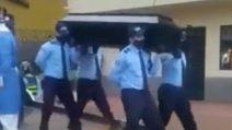 Poliziotti ballano portando una bara sulle spalle
