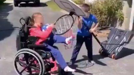 In sedia a rotelle non riesce a fare canestro: il fratello le dà subito una mano
