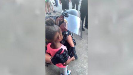 """La bimba impaurita al poliziotto: """"Mi sparerai?"""". L'agente si inginocchia e la tranquillizza"""