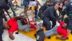Poliziotti scaraventano a terra un uomo sulla sedia a rotelle